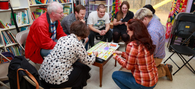 Large group of people play Co-opoly, laughing