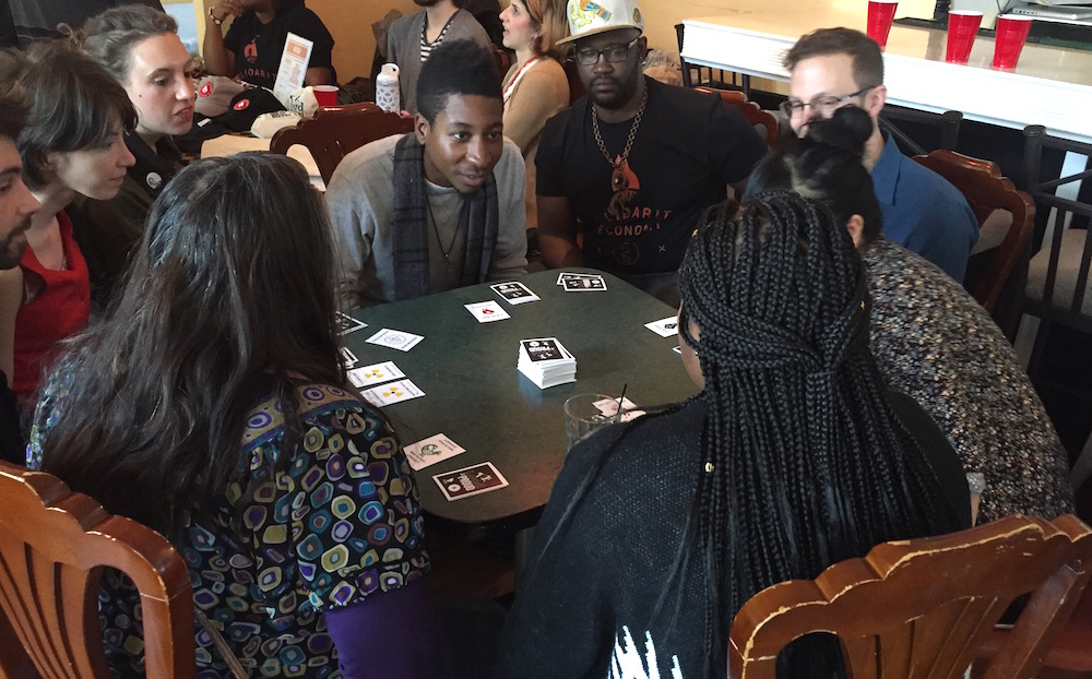 People sitting around a table and playing a card game