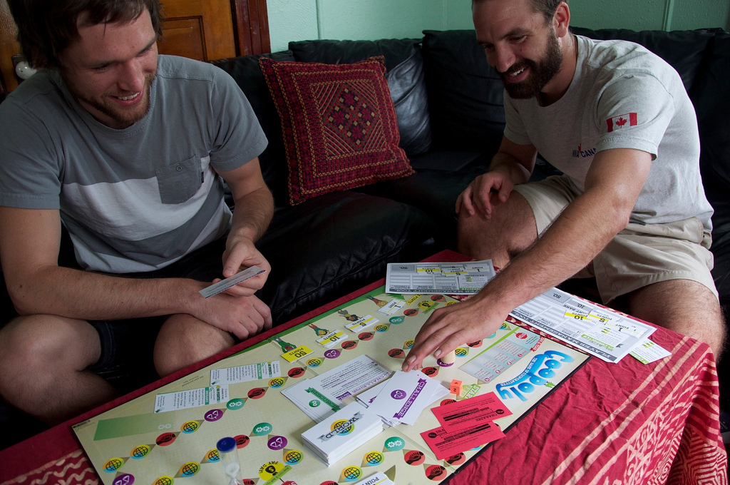 Two men sit at a coffee table playing a colorful board game, smiling